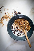 Peanut butter granola with cocoa nibs and chopped almonds and dark chocolate with milk on a marble table