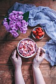Woman eating strawberry banana ice cream in a bowl topped with goji berries and cacao nibs