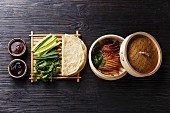 Peking Duck in bamboo steamer served with fresh cucumber, green onions, cilantro and roasted wheaten chinese pancakes