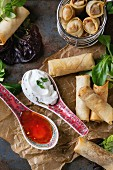 Fried spring rolls with red and white sauces in china spoons, served on crumpled paper and in fry basket with green salad and wooden chopsticks