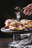 Homemade choux pastry cake Paris Brest with raspberries, almond and rosemary, served on black wooden serving board on cake stand