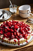 Strawberry tart with vanilla cream on a rustic wooden table