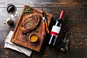 Grilled sliced Steak Rib eye with Pepper sauce and bottle of Red wine on wooden background