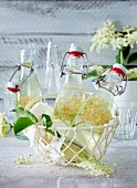 Elderflower syrup in small bottles in a wire basket
