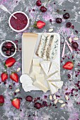 Cheese board, served with fresh fruits, strawberry jam, almonds and edible dried rose petals