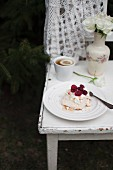 Mini Pavlova (meringue cake) with whipped cream, raspberries and almond flakes, served in the garden with cup of tea