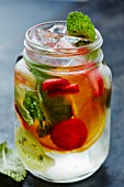 Water with fresh fruits, ice cubes and mint