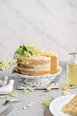 Elderflower cake on a cake stand, slice removed