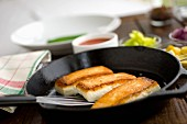 Fried halibut fillets in a pan