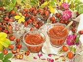 Two glasses of rosehip jam surrounded by roses
