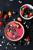 A berry smoothie bowl topped with strawberries and blueberries