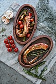 Octopus tentacles with tomatoes, peppers and herbs in rustic serving dishes