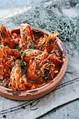 Gambas with garlic and tomato sauce and herbs in a rustic serving dish