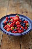 Frische Heidelbeeren, Erdbeeren und Himbeeren in Keramikschale