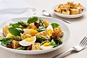 Bread salad with green asparagus, dried tomato, eggs and basil