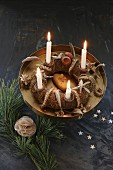 A homemade advent wreath with burning candles on a golden cake stand