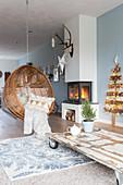 Hängesessel vor dem Kamin und im Wohnzimmer mit blauer Wand