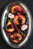 Grilled berries and peaches with mascarpone cheese cream in plate