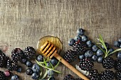 Berries blackberry and blueberry, honey on dipper, rosemary served over gray metal texture background