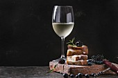Grilled sandwich with melted goat cheese, blackberry, blueberry, rosemary and honey, served on terracotta board with glass of cold white wine