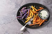 Variety of french fries traditional potatoes, purple potato, carrot served with white cheese sauce, salt, thyme on vintage tray