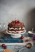 Black forest gateau on a cake stand with dark chocolate and cherries