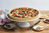 Spinach quiche with cherry tomatoes, raisins and pine nuts