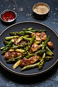 Fried green asparagus with chicken breasts in sweet and spicy sauce with sesame seeds