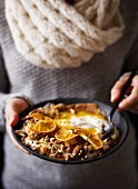 A woman holding an orange smoothie bowl with crunchy muesli and coconut butter