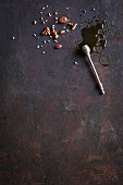 A honey dipper and various nuts on a dark background
