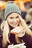 A young woman dressed for winter eating a waffle at a Christmas market