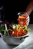Fresh carrots and herbs in a colander, with carrot juice in measuring cup