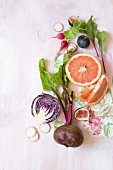 A still life with beetroot, figs, grapefruit, radishes, and red cabbage