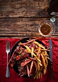 Sticky pork ribs with whiskey and maple syrup, served with sweet potato fries