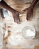 A pair of hands rolling out dough
