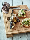 Slices of toast with smoked and grilled mackerel, green asparagus, cucumber, and dill mayonnaise