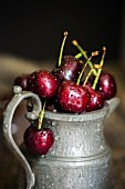 Freshly washed red summer cherries in a pewter jug