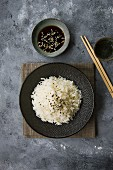 Boiled basmati rice with sesame seeds on a black plate (Asia)