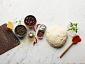 Ingredients for making pizza: pizza dough, anchovies, capers, olives, parmesan