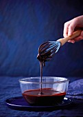 Chocolate sauce dripping from a whisk into a glass bowl