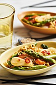 Asian noodles with green asparagus, spring onions, carrots, red peppers and sesame seeds
