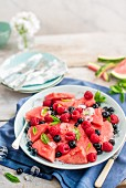 Fruit plate with watermelon slices, raspberries and blueberries with mint and ice cubes