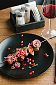 Beef on skewer with pomegranate seeds and red wine