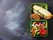 Thunfisch-Sandwich, griechischer Salat, Gemüse und Obst in Lunchbox