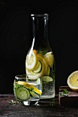 Citrus cucumber sassy sassi water for detox in glass bottle on dark black background