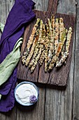 Fried breaded asparagus with almond flour and sesame seeds, and a herb dip