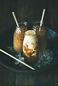 Thai-Eistee mit Milch in Glasflaschen vor dunklem Hintergrund