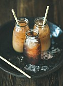 Cold Thai iced tea in bottles with milk on plate over dark wooden background