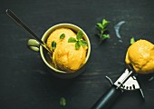 Mango sorbet ice cream scoops with fresh mint in green cup over black wooden background