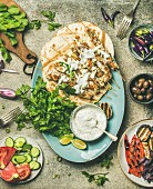 Flatlay of grilled chicken skewers with yogurt dip, flatbreads, fresh parsley, vegetables, marinated olives and chilis over grey concrete table background